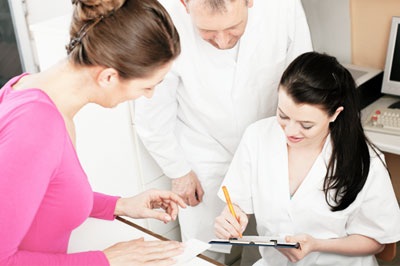 Front desk of medical office with receptionist and patient signing a clipboard