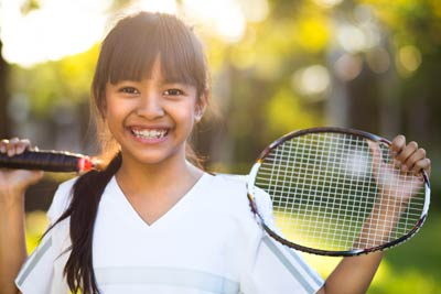 Young girl with tennis racket in need of a physical