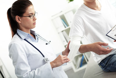 Female doctor providing urgent care services to person with hurt arm
